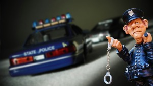 statuette cop with handcuffs and state trooper car in background